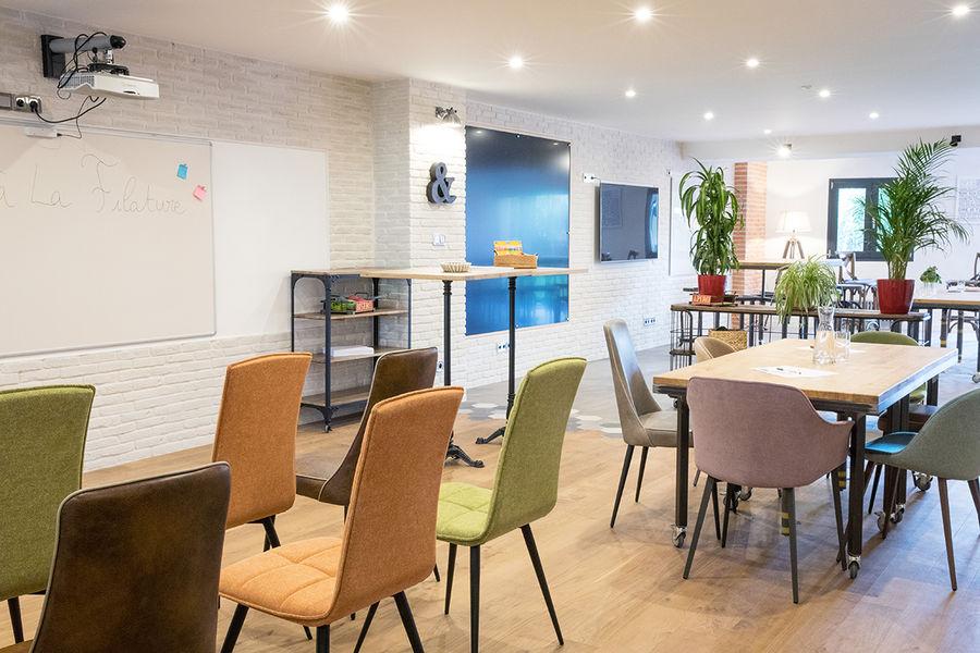 La Filature Parcours idéation,  différentes zone délimités en différentes configurations : table position haute, chaises en théatre, tables en réunion pour plusieurs groupes de travaile.