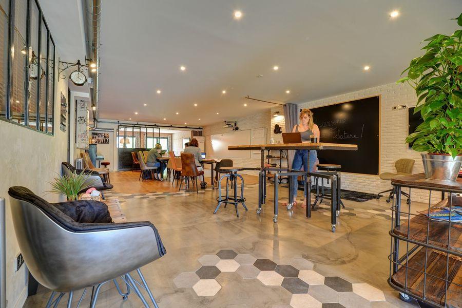 La Filature Dos au jardin et à l'entrée, voici une disposition en mode coworking, tables en position haute ou basse au choix.