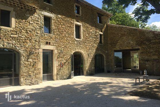 Une belle batisse en pierre et une vaste terrasse ombragée